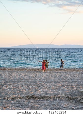 travel to Greece - children play on urban beach of Aegean Sea in Athens city in evening
