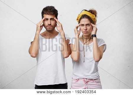 Portrait Of Bearded Handsome Man And Beautiful Woman With Yellow Headband On Head Trying To Concentr