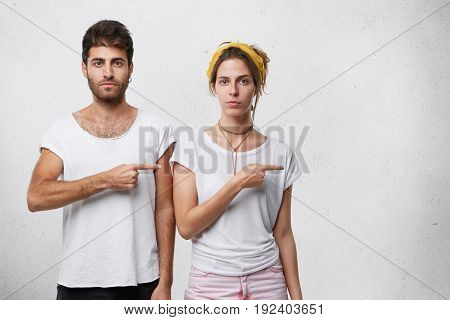 Young Couple In Love Dressed Casually Posing Against White Wall With Copy Space For Your Advertismen