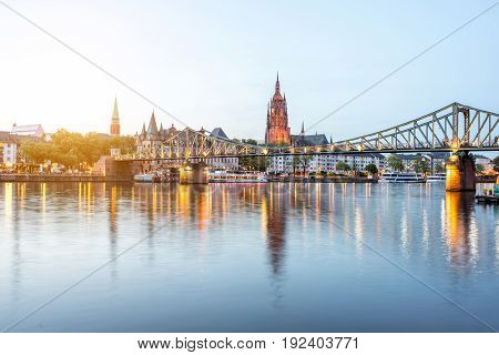 Beautiful cityscape view on the illuminated old town and bridge during the twilight in Frankfurt, Germany