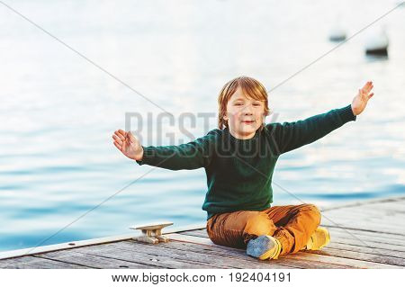 Outdoor portrait of adorable 5-6 year old boy resting by the lake wearing green pullover and yellow trousers arms wide open