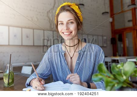 Beautiful And Cheerful Young Female Student Dressed In Stylish Clothes Smiling Broadly At Camera Whi