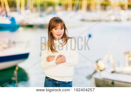 Outdoor portrait of pretty little girl posing by the lake wearing warm white pullover arms crossed