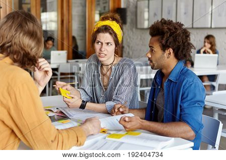 Pretty College Student Female With Yellow Scarf On Head Listening To Her Groupmates Disagreeing With