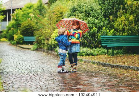 Two kids under umbrella wearing rain boots and jackets