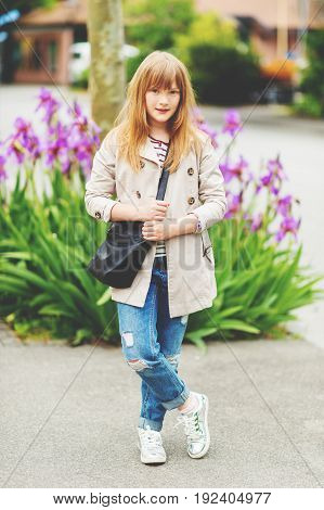 Young stylish hipster kid girl wearing modern trench coat posing outdoors
