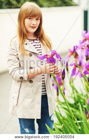 Outdoor fashion portrait of 9-10 year old hipster girl wearing stylish trench coat