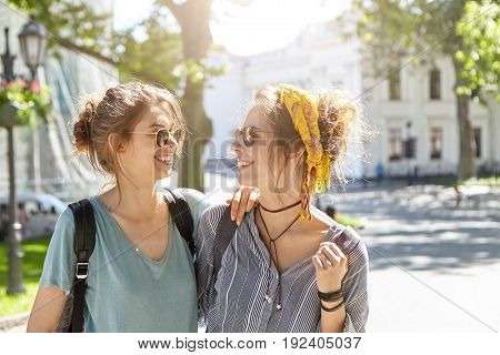 Two student female companions standing at campus during break gossiping about boys. Women in sunglasses holding backpacks going to university having good mood. Real friendship and support concept. poster