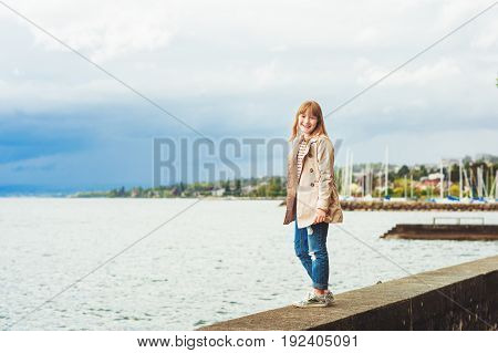 Cute little girl playing outside on a cloudy day, wearing beige stylish trench coat. Image taken on Lake Geneva, Lausanne, Switzerland