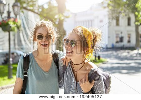 Outdoor Portrait Of Two Female Comrades Walking On Street Laughing While Talking With Each Other Enj