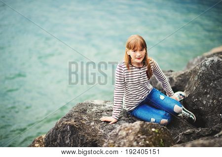 Adorable kid girl resting by the lake wearing stripe t-shirt and fashionable ripped jeans