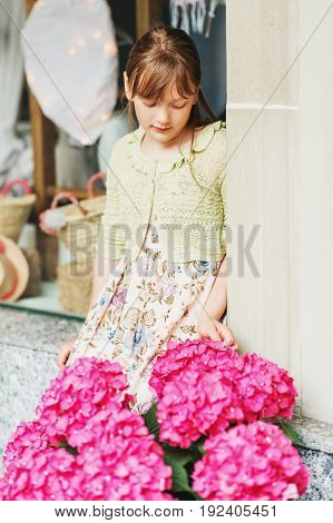 Outdoor portrait of pretty 9-10 year old girl wearing summer dress