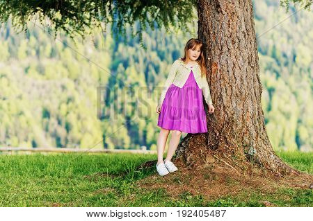Outdoor portrait of cute little girl resting in swiss mountains kid leaning on a big tree