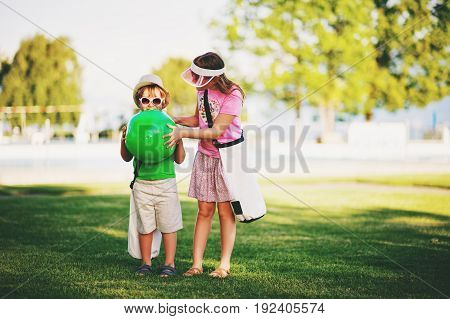 Two funny kids in green park. Little boy and girl ready to go to the pool on a hot summer day