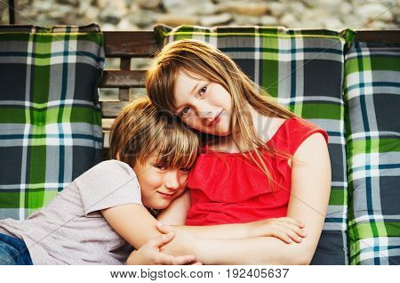 Two happy and joyful kids resting on swing bench