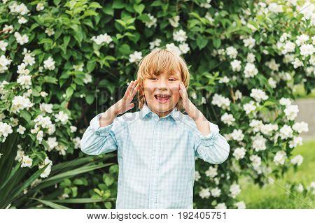 Adorable little kid boy playing in spring garden wearing light blue shirt summer fashion for children