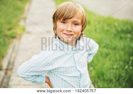 Outdoor portrait of adorable 6 year old boy wearing blue shirt