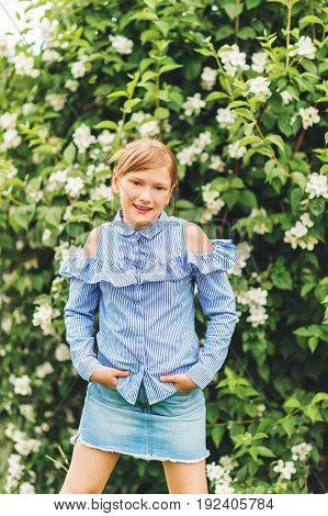 Adorable little kid girl playing in spring garden wearing light blue shirt and denim skirt summer fashion for children