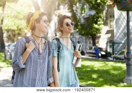 Happy Lesbian Couple Having Walk In Open Air Keeping Hands Together Admiring Sunshine With Great Ple