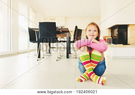 Pretty little girl sitting on the floor in new home wearing colorful socks