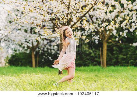 Pretty little kid girl dancing in spring blooming garden