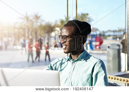 Stylish African Hipster Dressed In Shirt And Black Cap Sitting In Outdoor Cafe With Laptop Checking