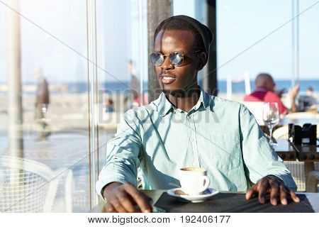 Portrait Of Smiling Dark-skinned Male Wearing Sunglasses, Cap And Shirt Sitting At Cafeteria Near Se