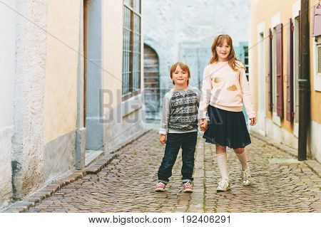 Outdoor portrait of adorable fashion kids, wearing sweatshirts, holding hands, walking together in a city