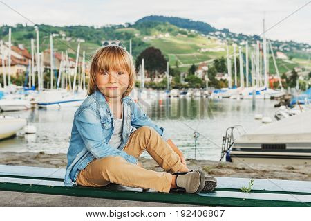 Outdoor portrait of adorable little boy resting on the bench in a beautiful small port on Lake Geneva Switzerland