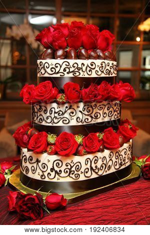Strawberry Chocolate Wedding Cake. A three tiered wedding cake decorated with chocolate dripped strawberries and red roses.