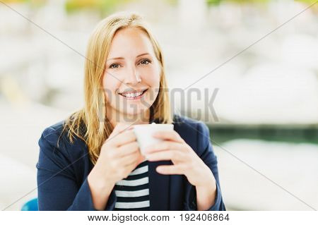 Beautiful blond woman having a break with cup of cofee oudoors