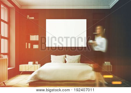 Blond woman in a modern luxury bedroom with black walls a large bed in the center of the room two bookcases by its sides a large window and a framed horizontal poster. 3d rendering mock up toned image