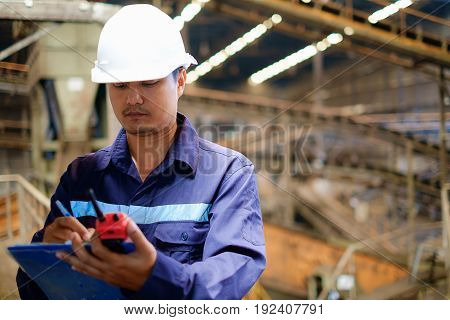 Engineer working in the production line process of coal screening plant, industrial concept