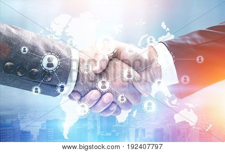 Close up of two businessmen shaking hands. Global network and a world map in the foreground. Toned image double exposure.