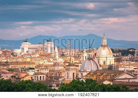 Panoramic aerial wonderful view of Rome with Altar of the Fatherland and churches at sunset time in Rome, Italy