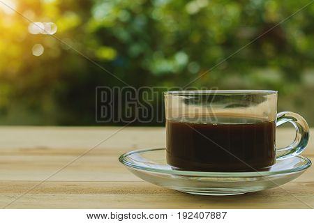 A cup of coffee on blurred green natural background with vintage retro color