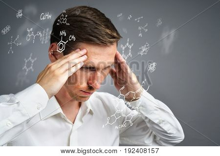 Man scientist in white shirt thinking about chemical formulas on gray background.