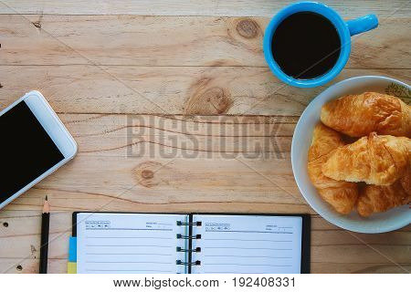 Top view of notebook a cup of coffee mini croissant bread mobile smartphoneand pencil on the wooden table, space for thinking and writing with the snack time