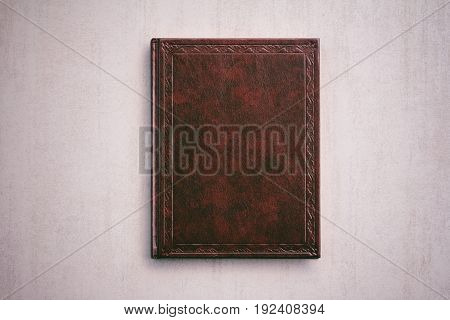 the book in a red cover on a light gray background top view