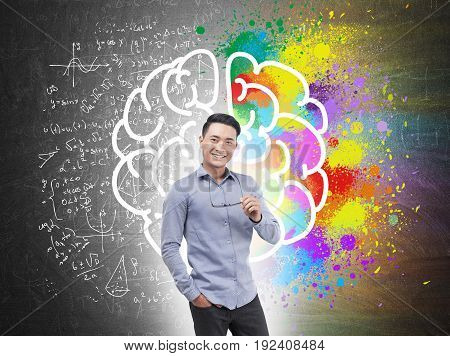 Portrait of a smiling Asian businessman wearing a blue shirt and dark trousers and holding glasses. Blackboard with a large brain sketch. A half is in formulas a half is colorful.