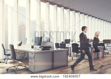 Side view of business people in an open space office interior with a wooden floor a panoramic window with shades rows of computer tables and office chairs. 3d rendering mock up toned image