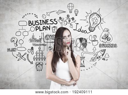 Portrait of a pensive businesswoman with dark hair. She is wearing a white shirt and standing near a concrete wall with a business plan sketch.
