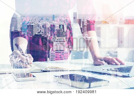 Close up of an unrecognizable young designer working in a white office. She is standing near her table and taking notes. Cityscape. Toned image double exposure