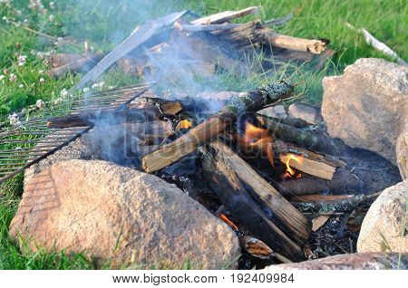 close on campfire between stones on the grass
