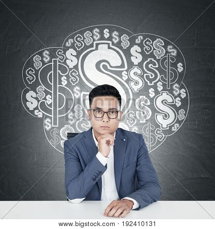 Portrait of a young Asian businessman wearing glasses and a blue suit and sitting at a table. Blackboard dollar sign cloud sketch