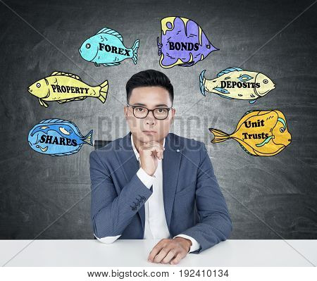 Portrait of a young Asian businessman wearing glasses and a blue suit and sitting at a table. Blackboard colorful fish with stock market buzz words