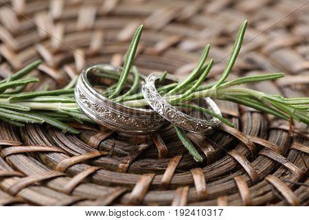 Ornate wedding bands displayed on a sprig of rosemary while laying on a weaved basket.