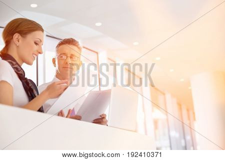 Business people discussing over documents in office