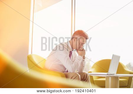 Side view of serious businessman looking at laptop in lobby