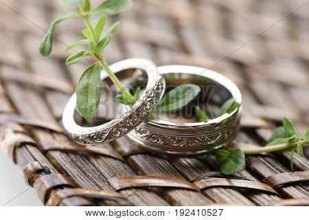 Wedding bands laying on a basket and a twig of thyme